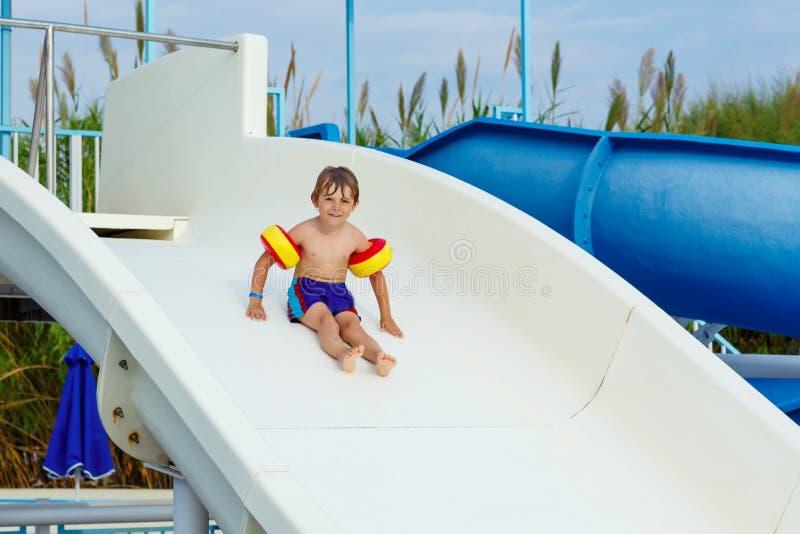 Ragazzino divertendosi sullo stagno del waterslide fotografie stock libere da diritti