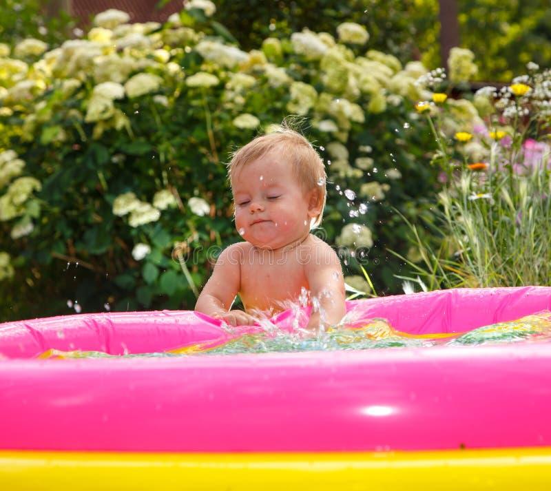Ragazzino divertente che gioca con acqua nello stagno del bambino fotografie stock libere da diritti
