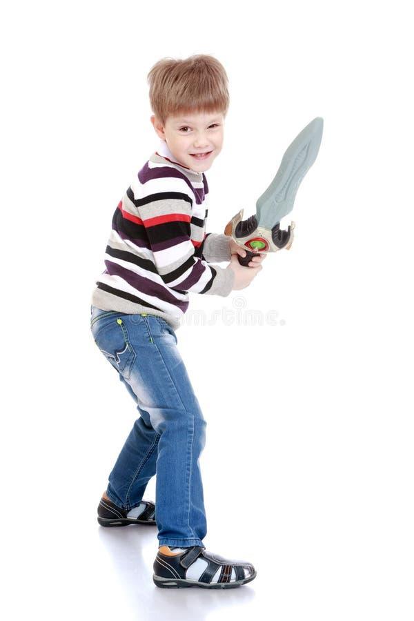 Ragazzino divertente con una spada del giocattolo a disposizione immagine stock