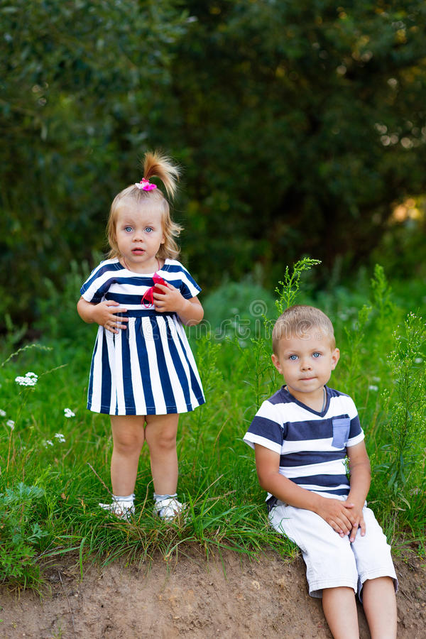 Ragazzino e ragazza che si siedono sull'erba all'aperto di estate fotografia stock libera da diritti