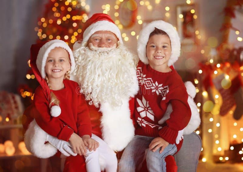 Ragazzino e ragazza svegli con Santa Claus nella sala fotografia stock