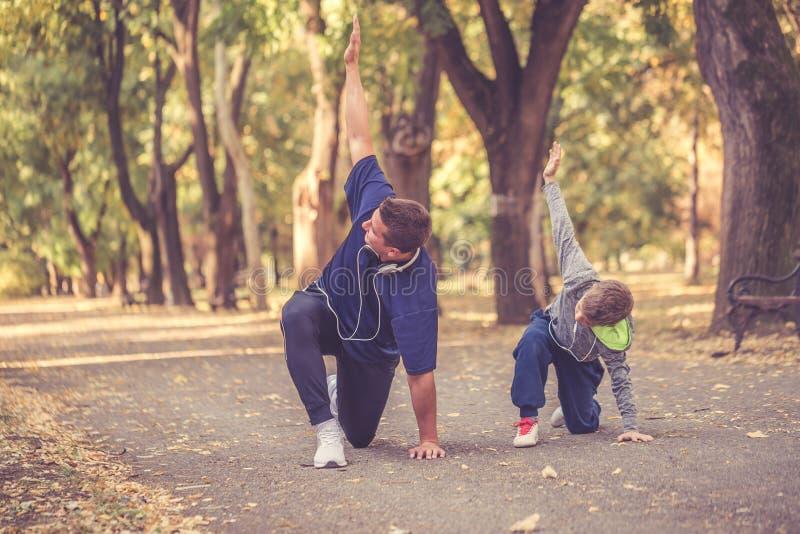 Ragazzino ed suo padre che fanno esercizio nel parco fotografia stock libera da diritti