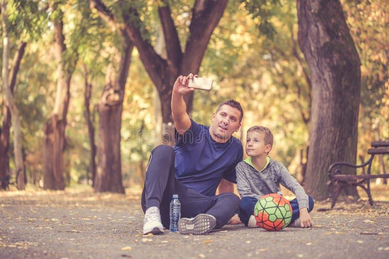 Ragazzino ed suo padre che prendono una rottura e che fanno selfie fotografie stock libere da diritti