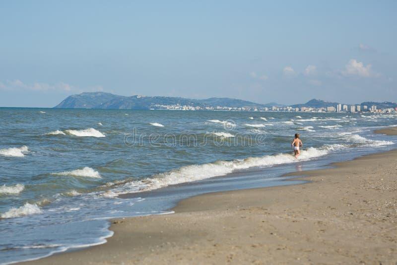 Ragazzino felice che corre lontano in acqua lungo la spiaggia del mare fotografia stock libera da diritti