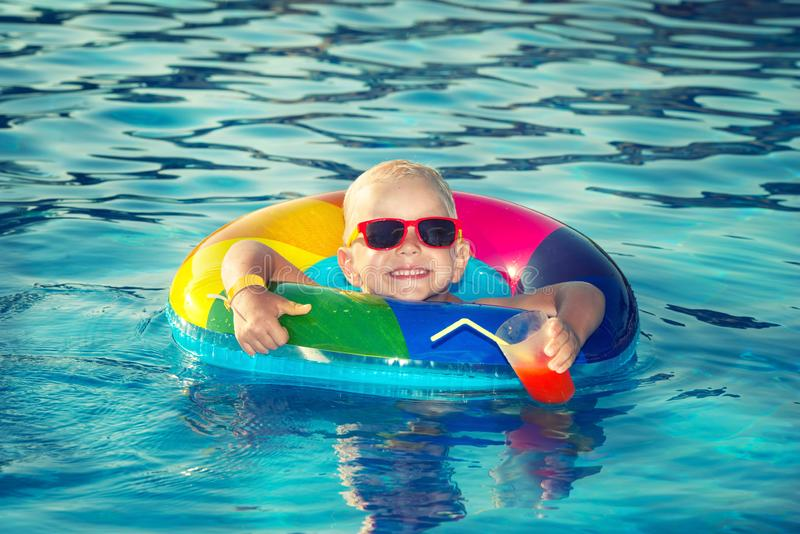 Ragazzino felice che gioca con l'anello gonfiabile variopinto nella piscina all'aperto il giorno e le bevande di estate caldi un  fotografia stock