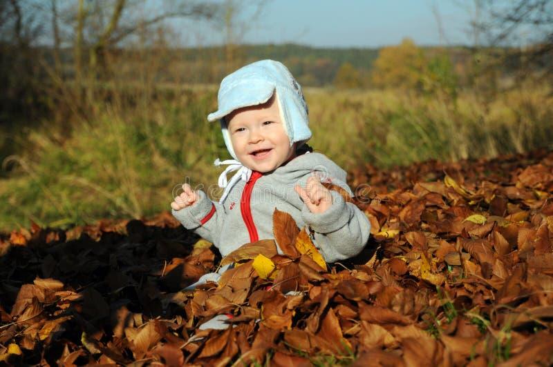 Ragazzino felice che gioca con l'autunno giallo fotografia stock libera da diritti