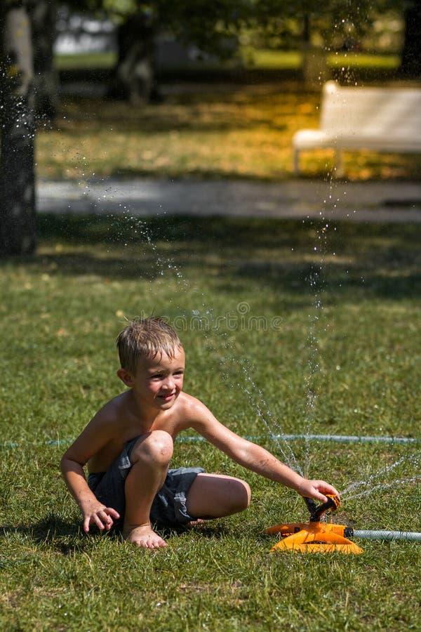 Ragazzino felice che gioca nelle gocce di acqua dal tubo flessibile di irrigazione, calore nella città fotografia stock
