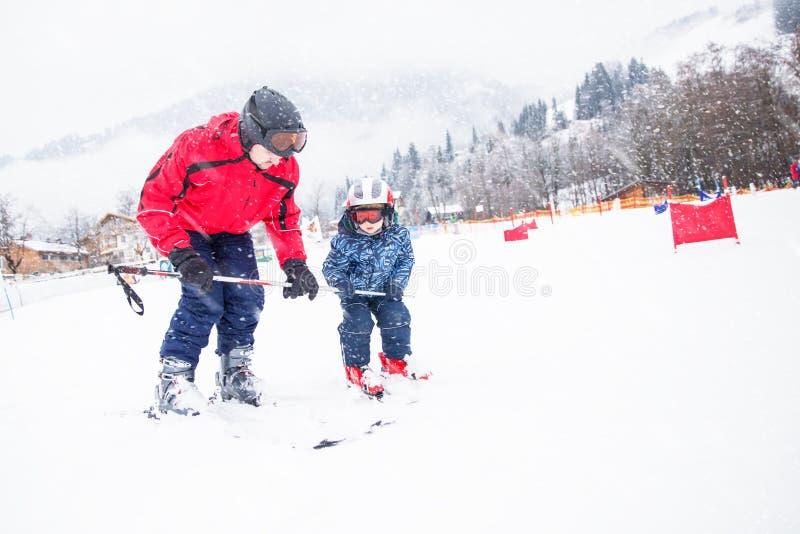 Ragazzino felice che impara corsa con gli sci con suo padre nella stazione sciistica di Kitzbuhel, Tirolo, Austria fotografia stock