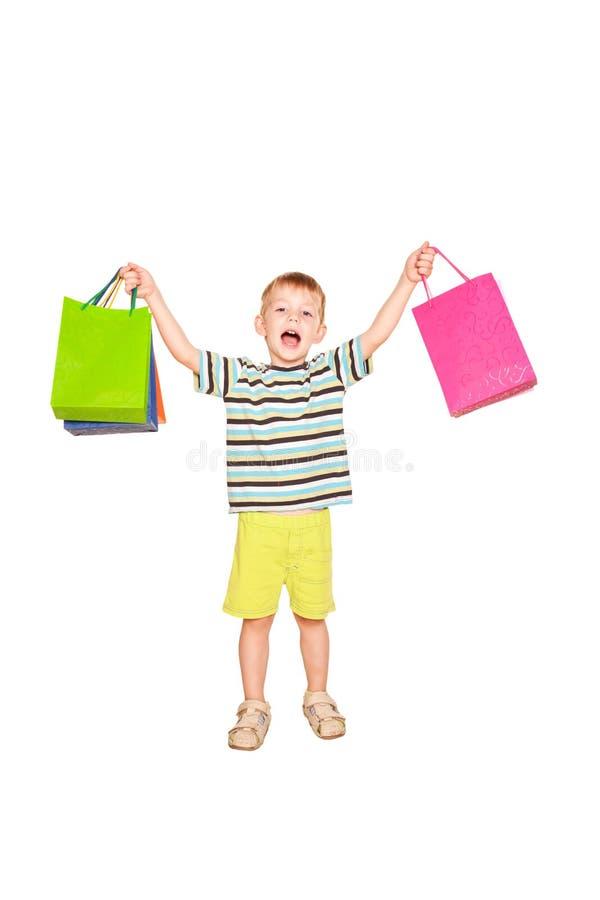 Ragazzino felice con i sacchetti della spesa. immagini stock libere da diritti