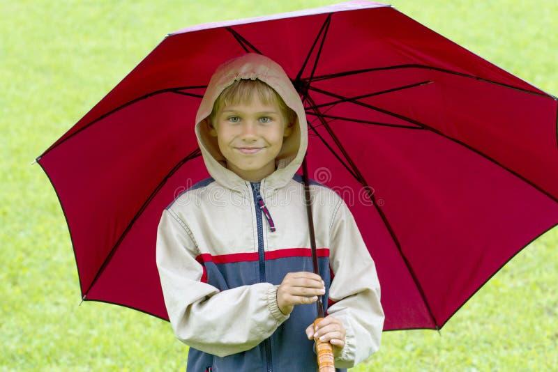 Ragazzino felice sotto un ombrello nella pioggia fotografia stock libera da diritti