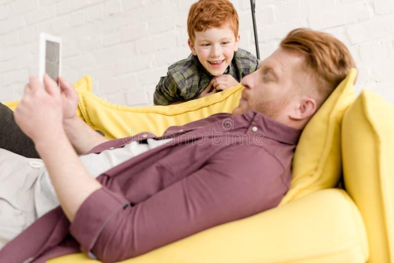ragazzino felice sveglio che esamina padre facendo uso della compressa digitale immagini stock libere da diritti