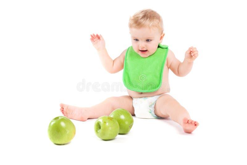 Ragazzino felice sveglio nel gioco verde della busbana francese con le mele fotografia stock