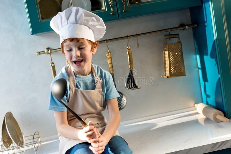 ragazzino felice sveglio in siviera del cappello del cuoco unico e della tenuta del grembiule immagini stock libere da diritti