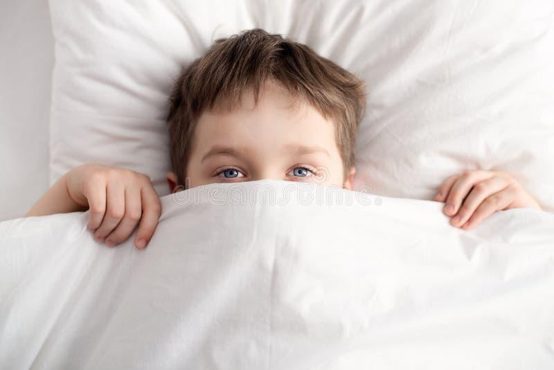 Ragazzino a letto che copre il suo fronte di coperta bianca immagine stock libera da diritti
