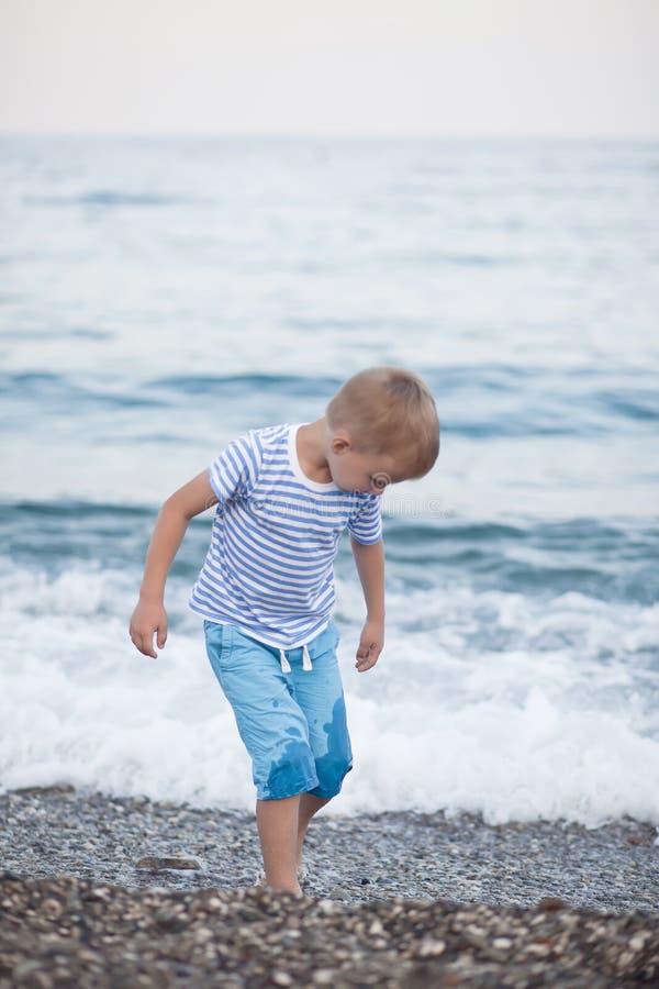 Ragazzino in maglietta a strisce che gioca sulla spiaggia con fondo confuso dal mare fotografia stock libera da diritti