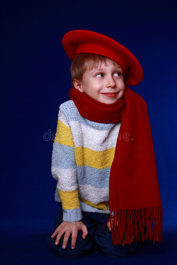 Ragazzino nel sorridere rosso del berreto e della sciarpa fotografia stock
