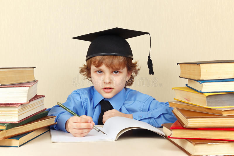 Ragazzino nella penna accademica di scrittura del cappello in taccuino fra i vecchi libri fotografie stock