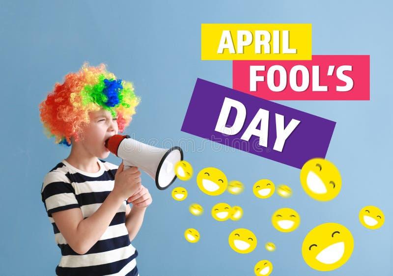 Ragazzino nella travestimento divertente e con il megafono sul fondo di colore Celebrazione del giorno dei pesci d'aprile fotografia stock
