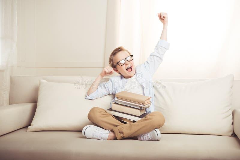 Ragazzino in occhiali che si siedono sul sofà con i libri che allungano e che sbadigliano fotografie stock