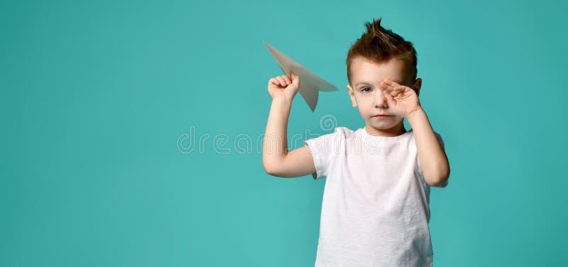 Ragazzino pronto a lanciare un aereo di carta ma smesso di sfregare occhio con la mano Nuovo punto inizio duro spazio del testo fotografie stock