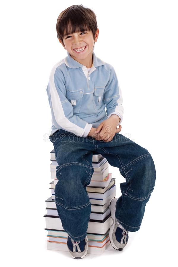 Ragazzino sorridente che si siede sopra il mucchio dei libri immagini stock libere da diritti