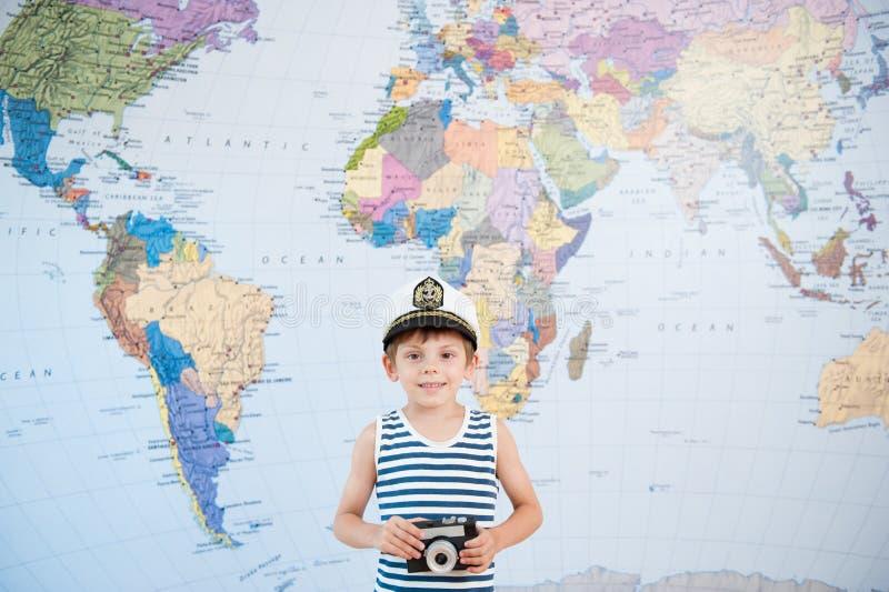 Ragazzino sorridente felice in cappuccio di capitano e camicia a strisce con la macchina fotografica vicino alla mappa immagine stock