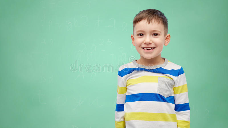 Ragazzino sorridente felice sopra il consiglio scolastico verde fotografie stock