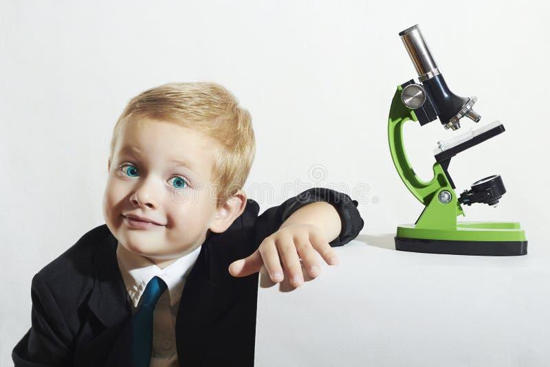 Ragazzino sorridente in legame Bambino divertente Scolaro che lavora con il microscopio Bambino astuto immagine stock libera da diritti