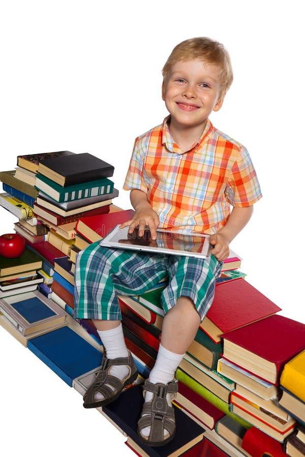 Ragazzino su un mucchio dei libri immagine stock
