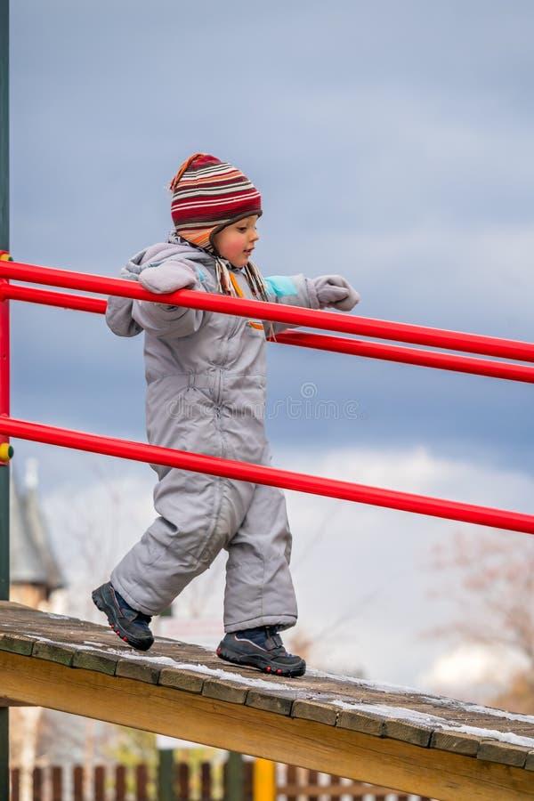 Ragazzino sul campo da giuoco nell'inverno fotografia stock libera da diritti
