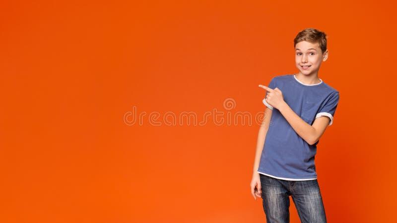 Ragazzino sveglio che indica via sul fondo arancio fotografie stock libere da diritti