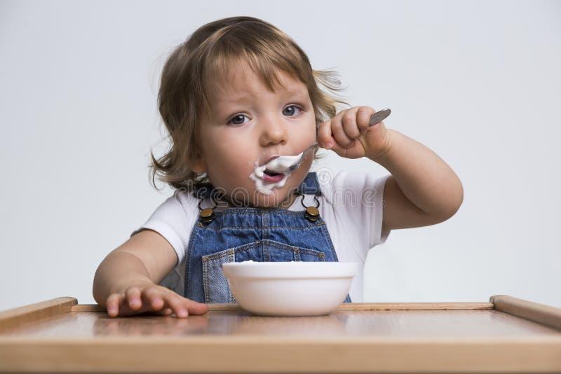 Ragazzino sveglio che mangia porridge fotografia stock libera da diritti