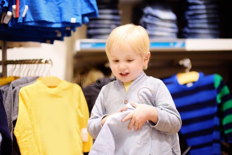 Ragazzino sveglio che sceglie i nuovi vestiti durante l'acquisto fotografia stock libera da diritti