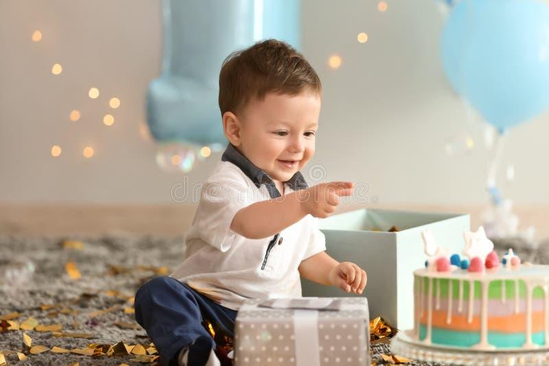 Ragazzino sveglio con il contenitore e la torta di compleanno di regalo che si siedono sul tappeto nella sala immagine stock libera da diritti