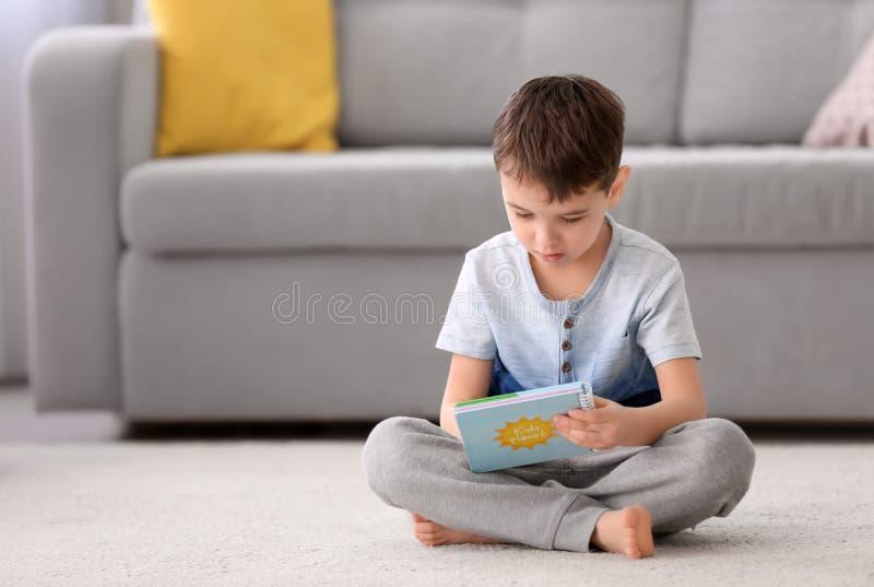 Ragazzino sveglio con il libro che si siede sul pavimento immagine stock