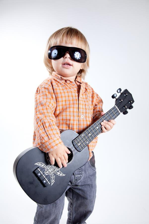 Ragazzino sveglio con la chitarra del ukulele fotografia stock