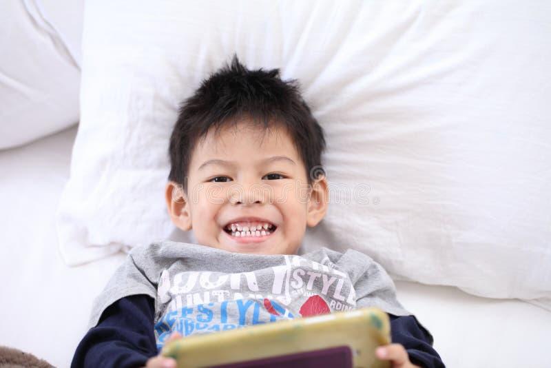 Ragazzino sveglio con la compressa digitale, presto imparante ragazzo asiatico pl immagini stock