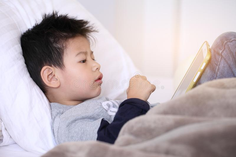 Ragazzino sveglio con la compressa digitale, presto imparante ragazzo asiatico pl fotografia stock libera da diritti
