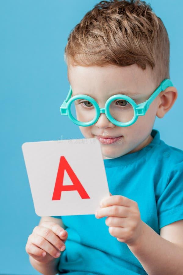Ragazzino sveglio con la lettera su fondo Il bambino impara le lettere Alfabeto fotografie stock libere da diritti