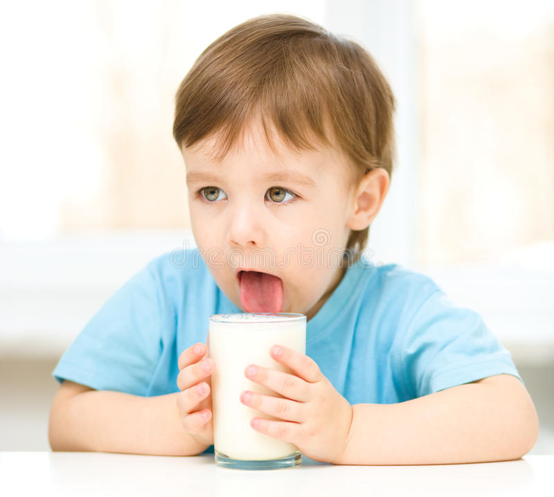 Ragazzino sveglio con un bicchiere di latte fotografie stock