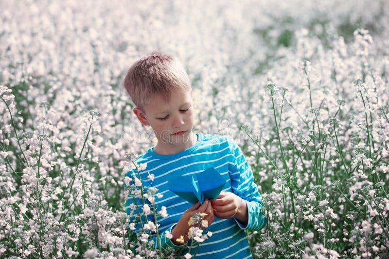 Ragazzino sveglio e felice che gioca con l'aeroplano di carta sul blosso fotografie stock
