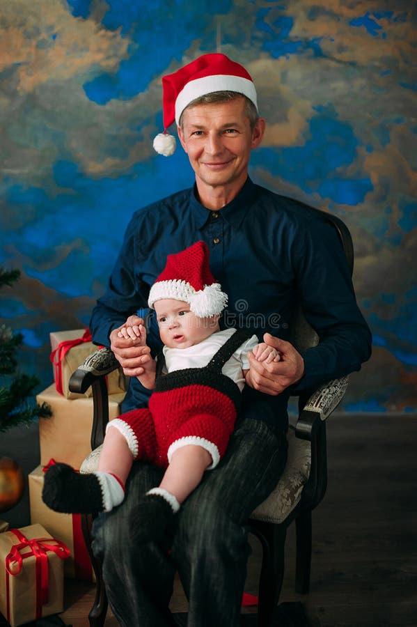 Ragazzino sveglio e suo il nonno che si siedono all'albero di Natale immagini stock libere da diritti