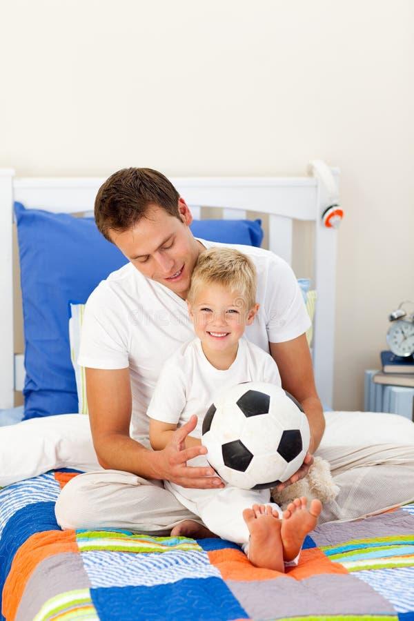Ragazzino sveglio e suo il padre che giocano con una sfera fotografia stock