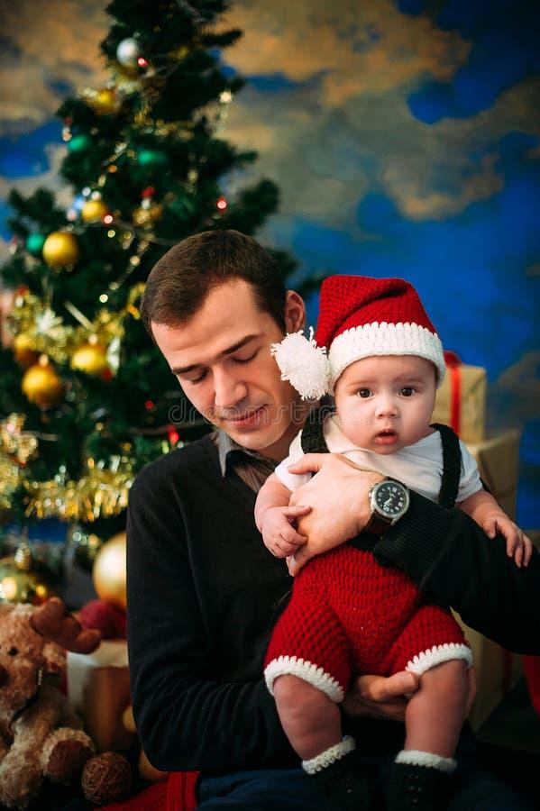 Ragazzino sveglio e suo il padre che si siedono all'albero di Natale fotografie stock