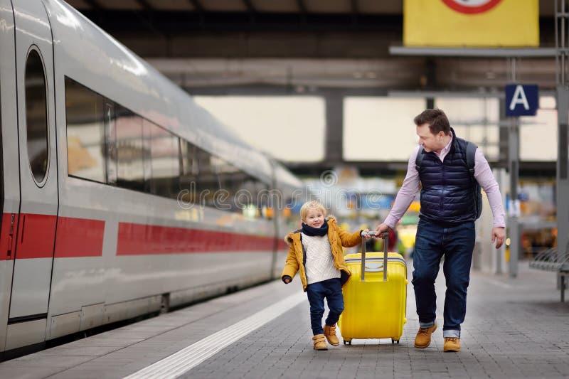 Ragazzino sveglio ed il suo treno espresso aspettante del padre sul binario della stazione ferroviaria fotografie stock libere da diritti