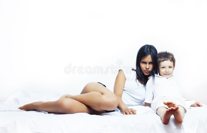 Ragazzino sveglio a letto con la madre in pigiami divertendosi sorridere felice, concetto della gente di stile di vita immagine stock libera da diritti