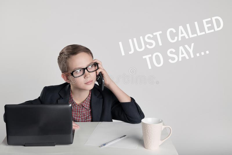 Ragazzino sveglio in un vestito che parla sul telefono immagini stock
