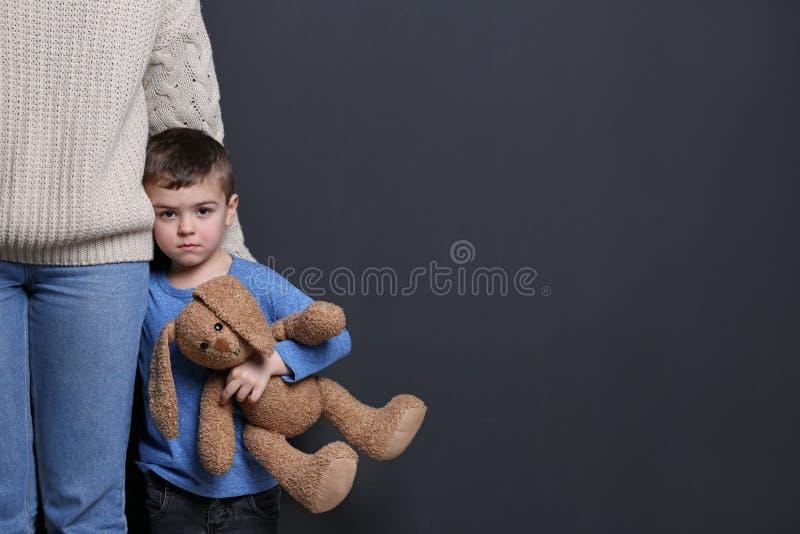 Ragazzino triste con il giocattolo che abbraccia sua madre su fondo nero fotografia stock libera da diritti