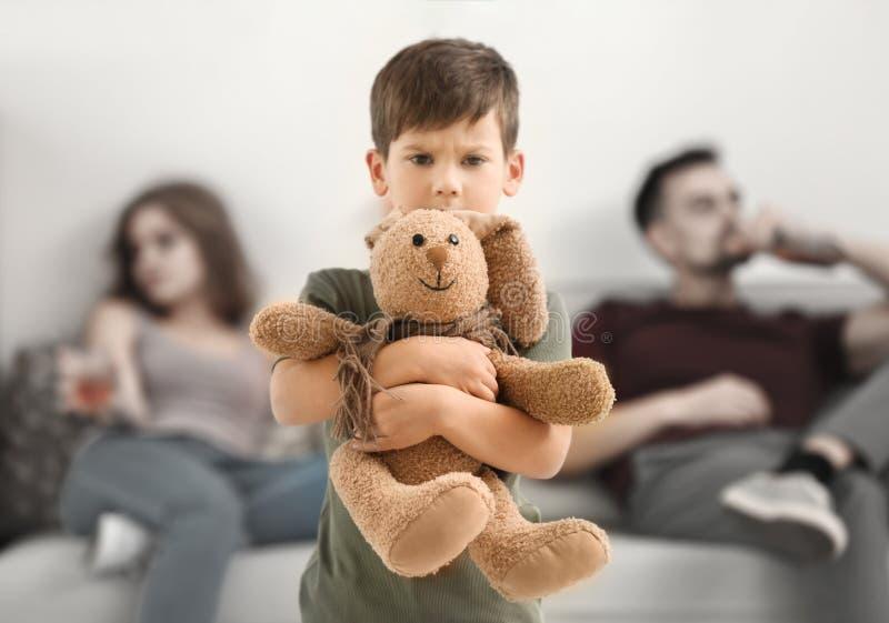 Ragazzino turbato che abbraccia il coniglietto del giocattolo mentre i suoi genitori che bevono alcool immagini stock