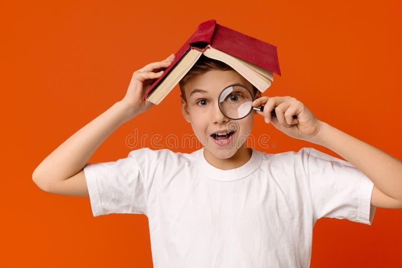 Ragazzo abile sveglio con la lente d'ingrandimento a disposizione che si nasconde sotto il libro fotografia stock